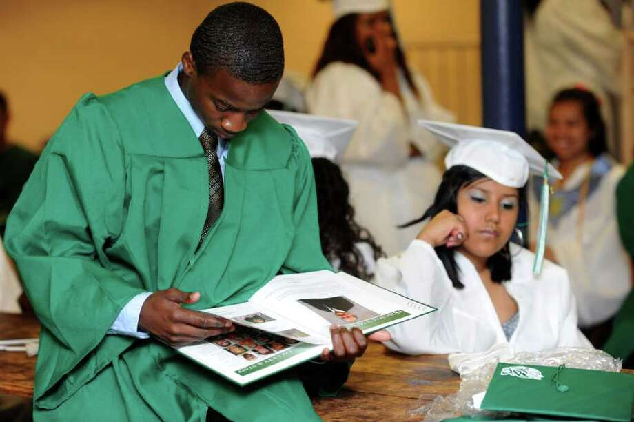 Roul Henry looks through a yearbook as students wait to begin Bassick High School's graduation ceremony at Klein Memorial Auditorium on Tuesday, June 21, 2011. Photo: Lindsay Niegelberg / Connecticut Post