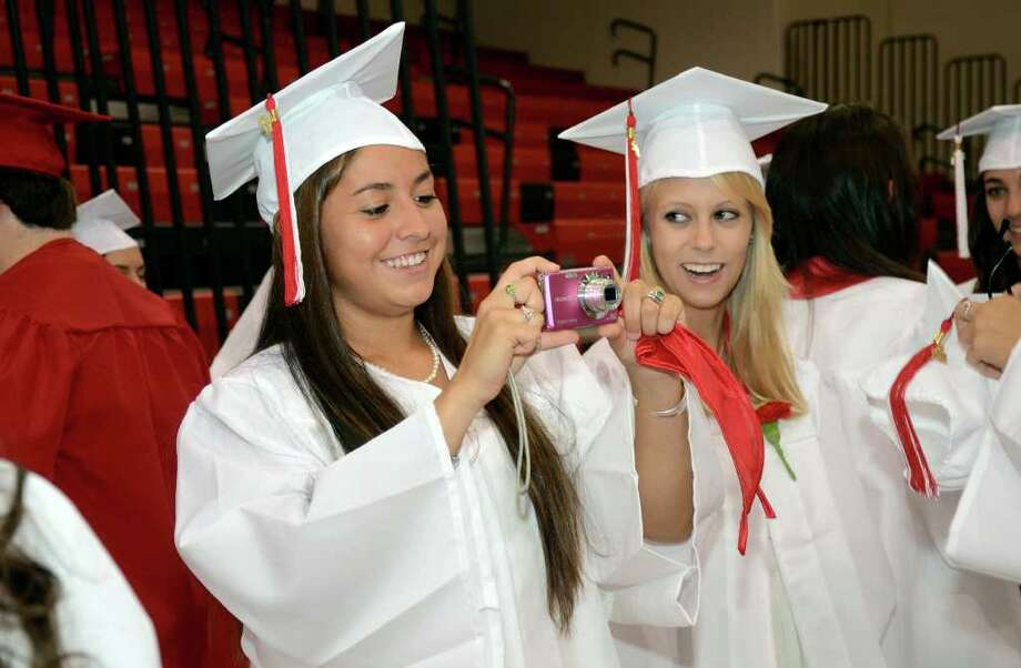Charlotte Stuifzand, at right, looks on as classmate Lauren Freeland takes a photo to memorialize their last moments as seniors in the New Canaan High School gymnasium during the 2011 New Canaan High School Commencement on Tuesday, June 21, 2011. Photo: Amy Mortensen / Connecticut Post Freelance