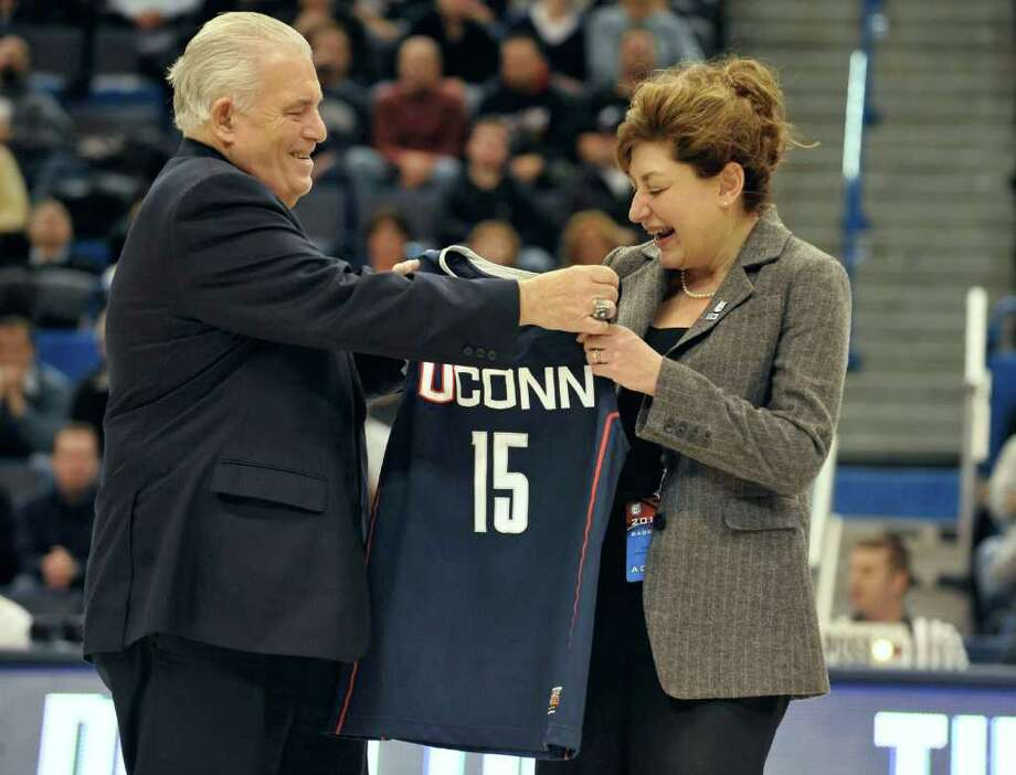 Larry McHugh, Chairman of the Board of Trustees at UConn, left, presents Susan Herbst, newly named 15th president of the University of Connecticut a Connecticut jersey during an NCAA basketball game in Hartford, Conn., Monday, Dec. 20, 2010.  (AP Photo/Jessica Hill) Photo: Jessica Hill, ST / AP2010