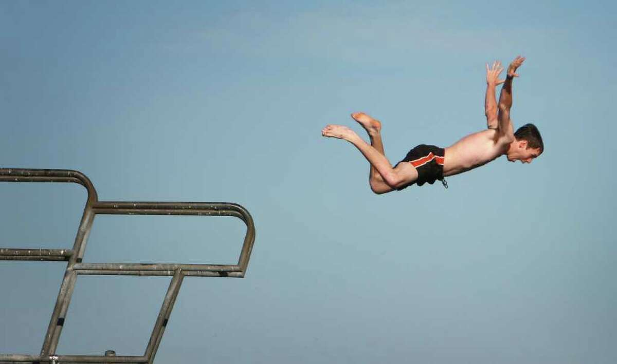 A diver leaps from a platform at Seattle's Green Lake Park on the first day of summer.