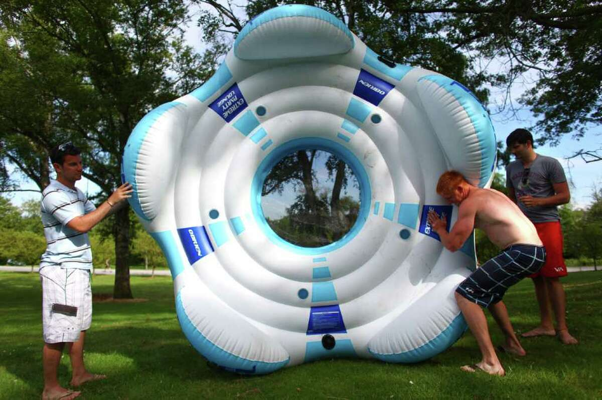 From left, Dylan Brauer, Matthew Horjus and Josef Reinke patch holes in their party lounge before launching at Seattle's Green Lake Park on the first day of summer.
