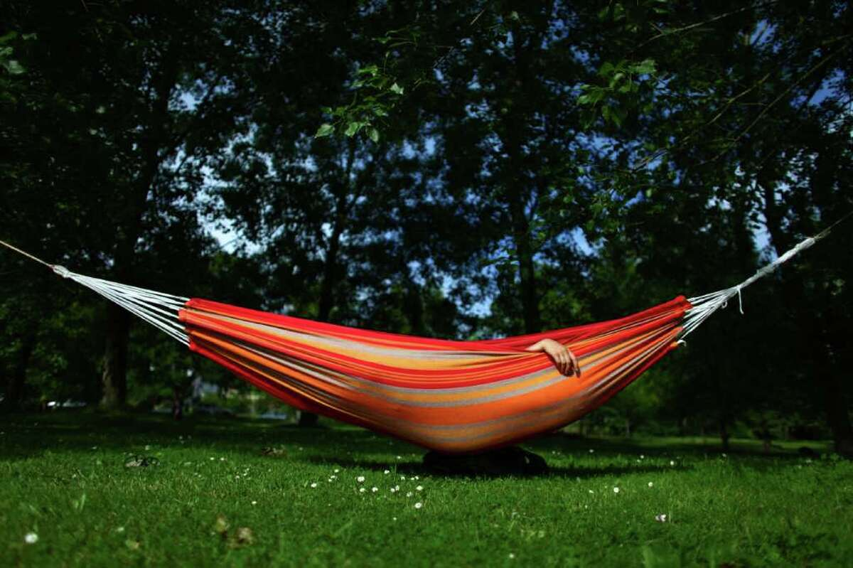 A woman sleeps in a hammock at Seattle's Green Lake Park on the first day of summer, Tuesday, June 21, 2011. Temperatures hovered in the mid 70s in the Emerald City on the summer solstice.