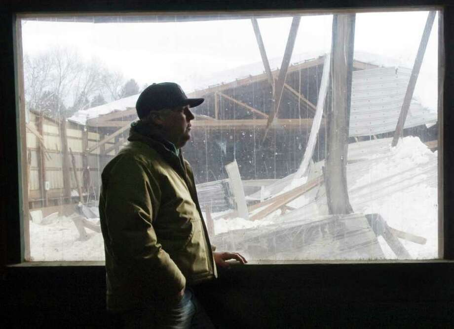Silvermine Farm owner Ken Markosky looks at the wreckage in his indoor riding arena on Thursday. The arena at his boarding stable in Norwalk collapsed under the pressure of snow on Thursday. Photo: Keelin Daly / Stamford Advocate