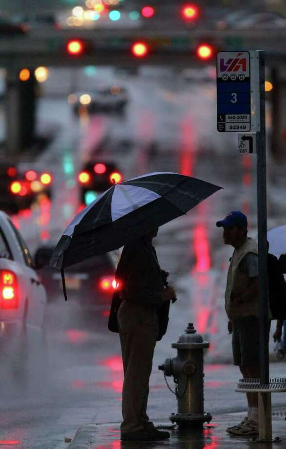Commuters woke to rain and cloudy skies for the first time in weeks in San Antonio as thunderstorms moved into the area overnight. These people at the corner of Heimer and Bitters (who would not release their identities when asked) were waiting for a bus shortly before 7:00 a.am. Wednesday June 22, 2011. Photo: JOHN DAVENPORT/jdavenport@express-news.net