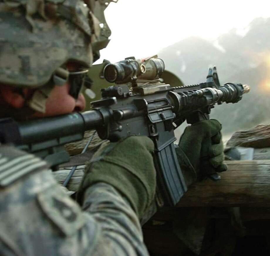 A soldier with 1st Battalion, 32nd Infantry Regiment, 10th Mountain Division, fires his assault rifle during a gun battle with insurgent forces in Afghanistan on July 12, 2009. President Obama will visit Fort Drum, NY - the 10th Mountain Division's home - Thursday after announcing a plan Wednesday night to withdraw troops from Afghanistan. AFP PHOTO/HO/US COALITION FORCES/MATTHEW C. MOELLER Photo: MATTHEW C. MOELLER, AFP/Getty Images / US COALITION FORCEs