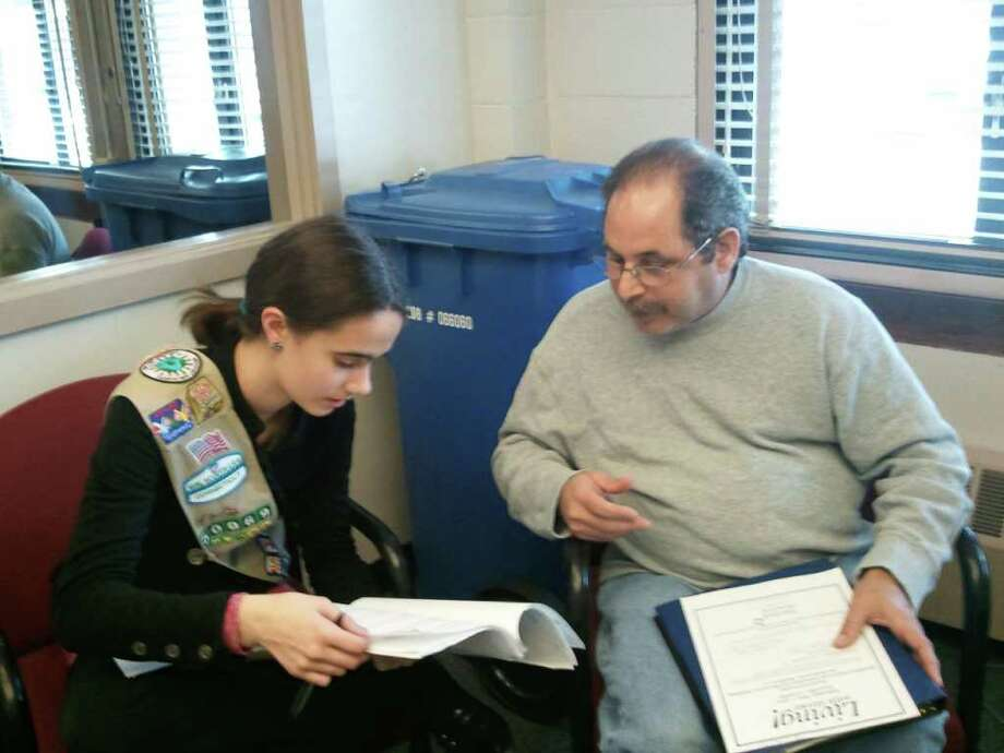 Sophie Call, who completed seventh grade this week, chats with Frank, a stroke survivor living with aphasia, at a New Haven clinic in April. Sophie is working toward her Silver Award, the middle school equivalent of the Boy Scouts' Eagle Scout award. Her community service project involves creating outlines of adult books for people with aphasia, a language disorder that affects the abilities to speak, understand, read and write. Photo: Contributed Photo / Westport News
