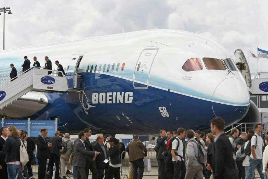 Visitors stand near the new Boeing 787 Dreamliner, on the third day of the Paris Air Show, at Le Bourget airport, north of Paris, Wednesday June 22, 2011.(AP Photo/Remy de la Mauviniere) Photo: REMY DE LA MAUVINIERE, ASSOCIATED PRESS / AP2011
