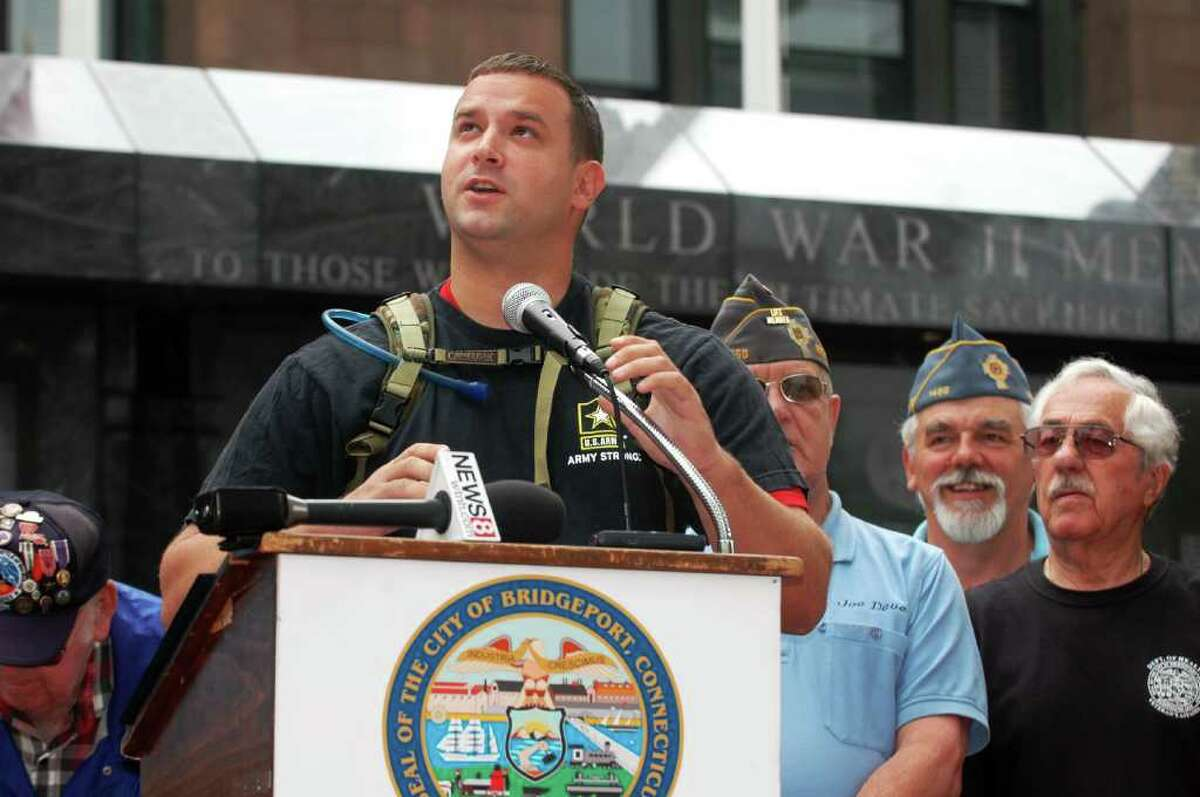 Troy Yocum, looks to the sky as he realizes he will be walking in the rain today. Yocum, an Iraq War Veteran in the midst of a 7,000 mile fundraising hike across the country, stopped at the War Memorials in Bridgeport, Conn. on Wednesday June 22, 2011. Many local veterans came by to thank him, on left is Joe Minto, to right is Joe LaFontaine, Al Neudeck and Ed Mastrone