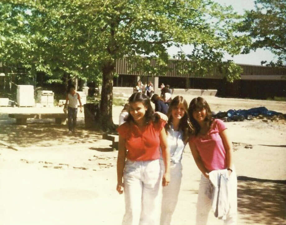 Three members of the Staples High School Class of 1981 stand in a courtyard that includes stacks of concrete and a pile of rubble. The entire class endured construction throughout its time at Staples and was recently given news that a planned clambake at the school, for a 30th reunion, cannot take place. At left is Aleda (Santos) Warren, a member of the Class of 1981's reunion committee. Photo: Contributed Photo / Westport News