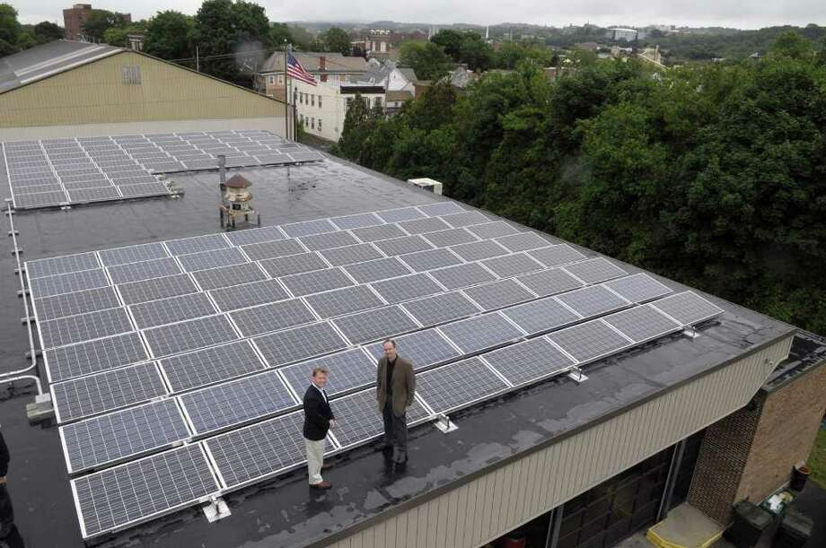 Watervliet Mayor Michael Manning, left, and consultant Jim Yienger pose on top of the city's fire department building that is equipped with solar panels on Tuesday morning, June 14, 2011 in Watervliet.  The city has undertaken projects to help reduce its carbon footprint. (Paul Buckowski / Times Union) Photo: Paul Buckowski  / 00013516A