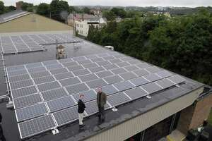 Watervliet Mayor Michael Manning, left, and consultant Jim Yienger pose on top of the city's fire department building that is equipped with solar panels on Tuesday morning, June 14, 2011 in Watervliet.  The city has undertaken projects to help reduce its carbon footprint. (Paul Buckowski / Times Union)