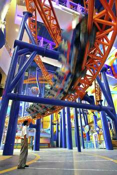 A man watches a roller coaster zoom past at the new Cosmo's World theme park in Kuala Lumpur in 2003. Cosmo's World is Malaysia's largest indoor theme park, covering 380,000 square feet. Photo: JIMIN LAI, AFP/Getty Images / 2003 AFP