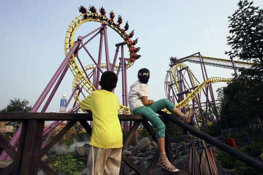 People watch a roller coaster at Happy Valley theme park in Beijing, China, in 2006. Photo: China Photos, Getty Images / 2006 Getty Images