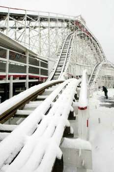 A worker shovels snow in front of the Coney Island Cyclone roller coaster during a snow storm Feb. 22, 2008, in Brooklyn, N.Y. Photo: Mario Tama, Getty Images / 2008 Getty Images