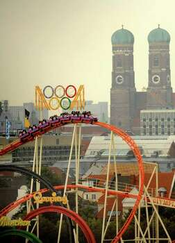 Visitors of the Oktoberfest beer festival enjoy a ride on a roller coaster on Sept. 23, 2008, in Munich, Germany. In background is Munich's landmark Frauenkirche, or Church of Our Lady. Photo: JOERG KOCH, AFP/Getty Images / 2008 AFP