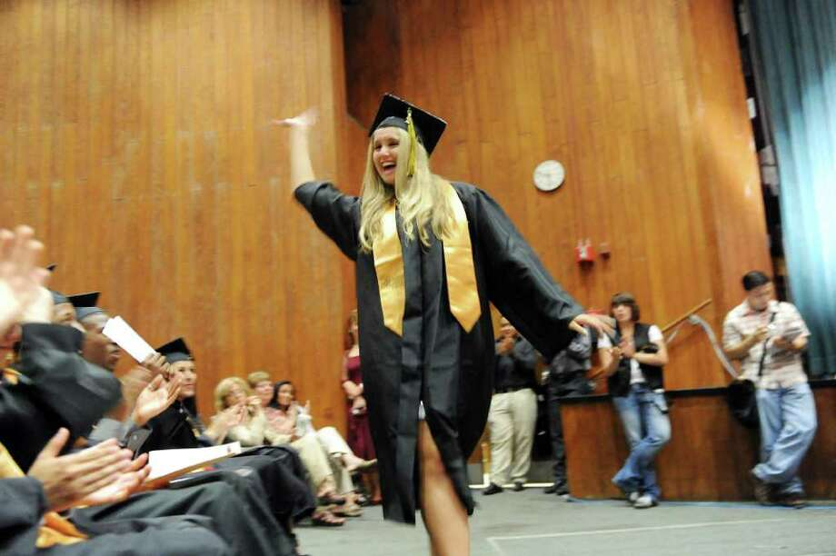 Morgan Castros waves to the cheering crowd as she heads for the stage to collect an award as the Academy of Information Technology & Engineering holds its 2011 commencement exercises inside the Rippowam Auditorium in Stamford, Conn., June 22, 2011. Photo: Keelin Daly / Stamford Advocate