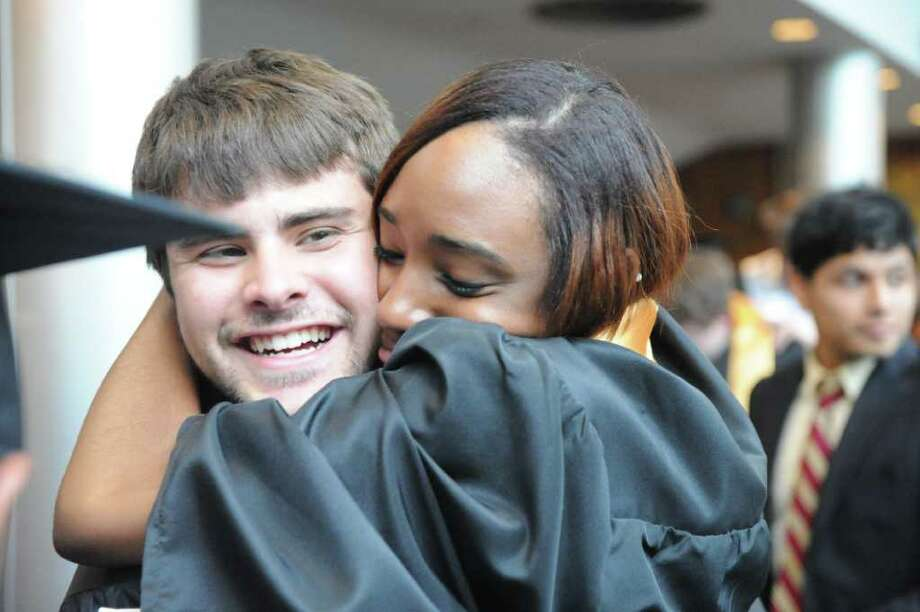 Carlos Albino gets a hug from fellow graduate Shereece Dennis as the Academy of Information Technology & Engineering holds its 2011 commencement exercises inside the Rippowam Auditorium in Stamford, Conn., June 22, 2011. Photo: Keelin Daly / Stamford Advocate