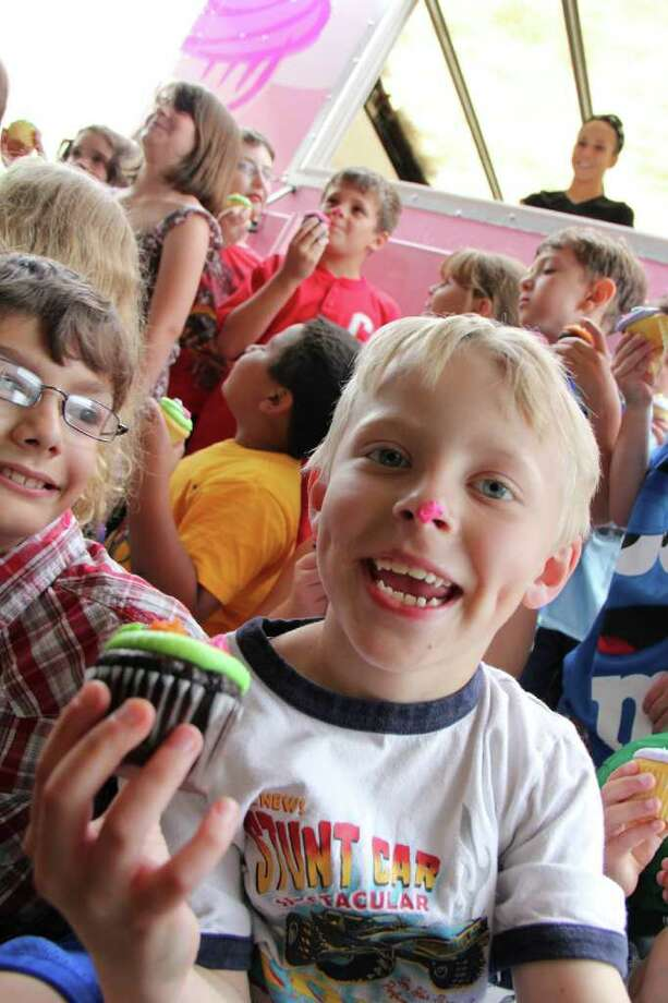 Dillon Wilkonson, age 7, front, and his fellow students at Veeder Elementary school hold cupcakes that were given away by Coccadotts Cake Shop, Colonie, at the school on Wednesday, June 22, 2011. Coccadotts held a facebook contest in which followers could vote for their favorite local school. Veeder Elementary won and more than 500 cupcakes of eight different flavors were delivered to students and faculty. (Erin Colligan / Special To The Times Union)