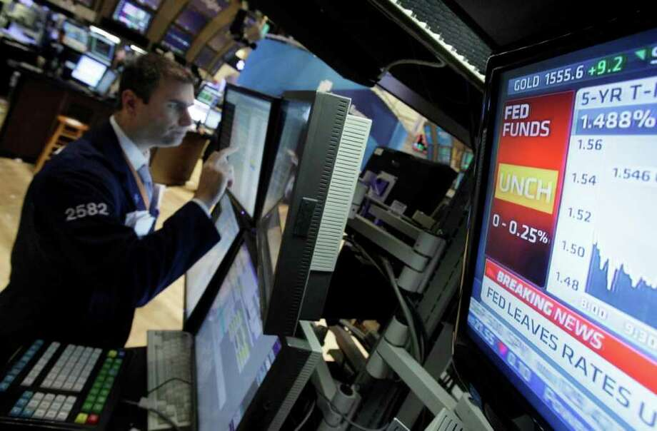 A television monitor shows the interest rate decision of the Federal Reserve as specialist Philip Finale works on the floor of the New York Stock Exchange Wednesday, June 22, 2011. The Federal Reserve acknowledged that the economy is growing more slowly than it expected. But it plans to complete its $600 billion Treasury bond buying program by the end of the month. (AP Photo/Richard Drew) Photo: Richard Drew