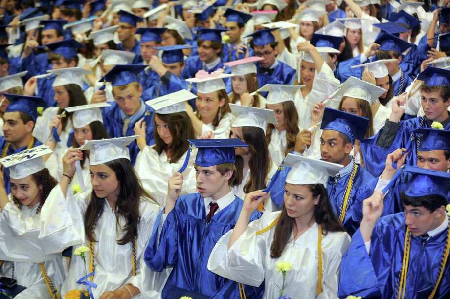 Newtown High School graduates move their tassels at the conclusion of commencement exercises, Wednesday, June 22, 2011. The graduation was held at Western Connecticut State University's O'Neill Center. Photo: Carol Kaliff / The News-Times