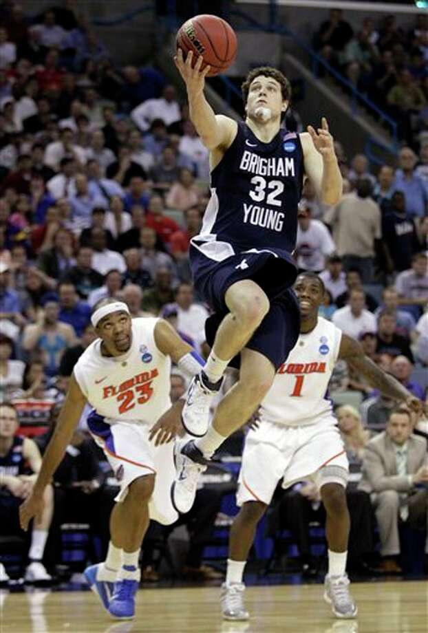 BYU's Jimmer Fredette (32) goes up for a shot in front of Florida's Alex Tyus (23) and Kenny Boynton (1) during the second half of the NCAA Southeast regional college basketball semifinal game in New Orleans. Fredette is a top prospect in the 2011 NBA draft. (AP Photo/Patrick Semansky)  2011 NBA draft Photo: Associated Press