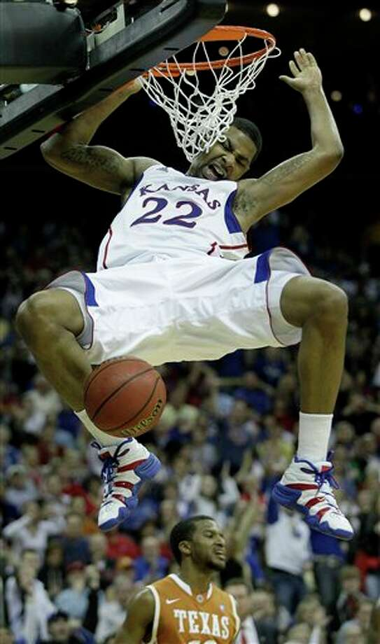 Kansas forward Marcus Morris (22) dunking in front of Texas guard Jai Lucas during the second half of an NCAA college basketball game, for the championship of the Big 12 men's basketball tournament,  in Kansas City, Mo. Morris is a top prospect in the 2011 NBA Draft (AP Photo/Charlie Riedel)  2011 NBA draft Photo: Associated Press