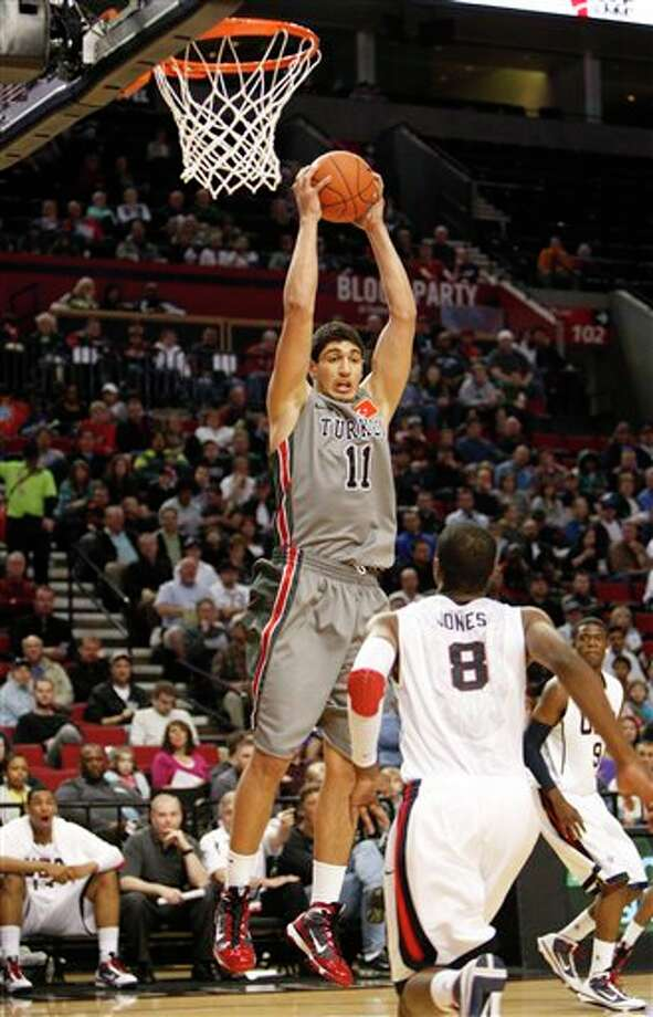 World Select Team's Enes Kanter (11), of Turkey, pulling down a rebound as Junior National Select Team's Terrence Jones (8) looks on in the first quarter during the Nike Hoop Summit, in Portland, Ore. Kanter is a top prospect in the 2011 NBA draft.  (AP Photo/Rick Bowmer) Photo: Associated Press
