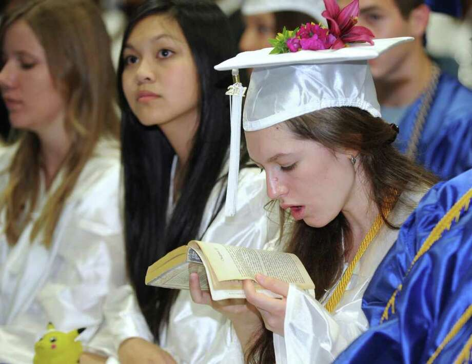 Eliana Kohrman-Glaser catches up on her reading during her graduation ceremonies from Newtown High School Wednesday, June 22, 2011. Seated next to her from left are, Abby Lee and Amy Kung. The commencement exercises were held at Western Connecticut State University's O'Neill Center. Photo: Carol Kaliff / The News-Times