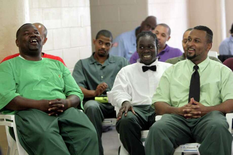 Gerald Harrison, right, and other inmates laugh during their graduation ceremony at  Sing Sing Correctional Facility, Wednesday, June 22, 2011 in Ossining, N.Y. More than 50 inmates at New York's Sing Sing prison have graduated from in-house courses designed to help them be better husbands and fathers both during their prison terms and after they're released.(AP Photo/Mary Altaffer) Photo: Mary Altaffer