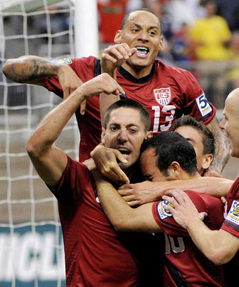 United States' Clint Dempsey, bottom left, is congratulated by teammates after scoring a goal against Panama during the second half of a CONCACAF Gold Cup semifinal soccer match Wednesday, June 22, 2011, in Houston. (AP Photo/Dave Einsel) Photo: Dave Einsel