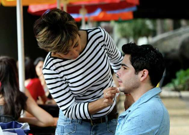 Pablo Magallanes has his makeup applied by Beatriz Pena (tilde on the n) Trujillo in preparation for filming of Dos Hogares on Thursday June 16, 2011 on the Riverwalk. Photo: HELEN L. MONTOYA, HELEN L. MONTOYA/hmontoya@conexionsa.com / SAN ANTONIO EXPRESS-NEWS