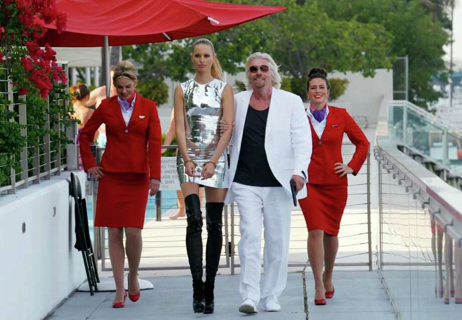 Richard Branson, second from right, president of Virgin Atlantic Airways, and supermodel/actress Karolina Kurkova, second from left, walk to a news conference after a photo-op, Thursday, June 16, 2011 in Miami Beach, Fla. Branson announced that Virgin is launching its 33rd destination with flights between London and Cancun, Mexico. Photo:  (AP Photo/Ric Francis)