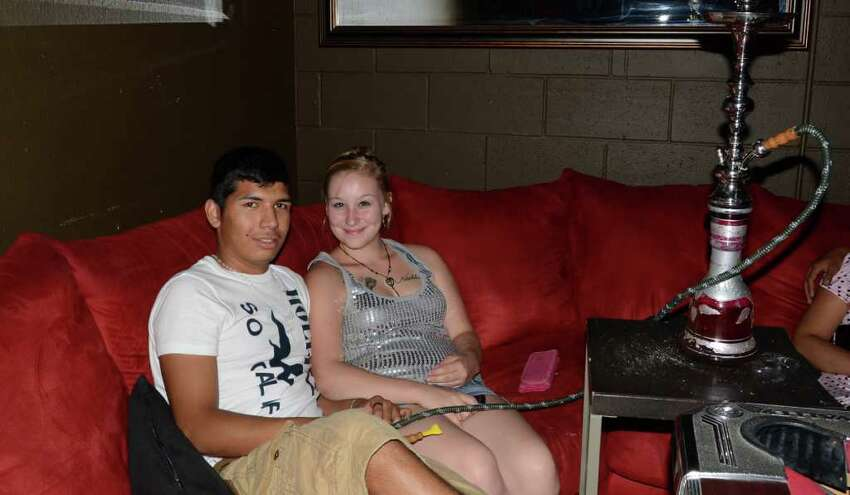 Yonathan Martinez and Janine Reynolds smoke their hookah while listening to live music at Studio 13. ROBIN JOHNSON / SPECIAL TO THE EXPRESS-NEWS