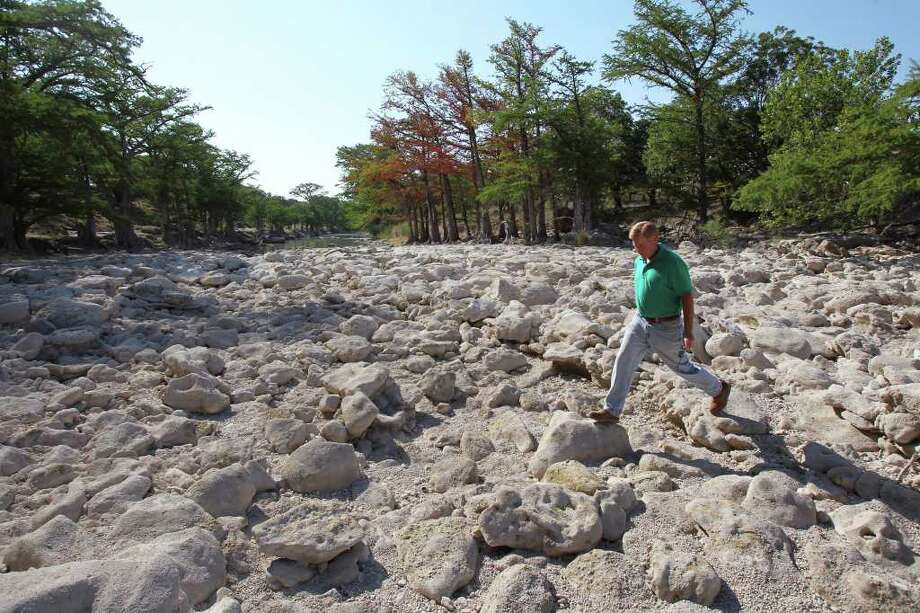 Landowner Bret Barnett strides across dry rocks in the Guadalupe River near FM 311 and the River Point subdivision. Photo: Tom Reel/treel@express-news.net / © 2011 San Antonio Express-News