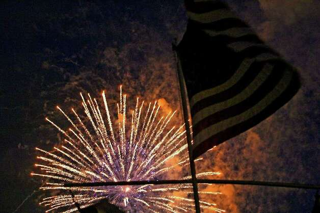 METRO   The flag flown by the Woodlawn Sail Club stands against fireworks on the lake Wednesday night during Fourth of July celebrations. Photo: TOM REEL, Tom Reel/Staff / SAN ANTONIO EXPRESS-NEWS