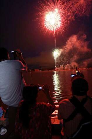 Spectators record the start of the Woodlawn Lake fireworks display with camera phones Wednesday night. Photo: TOM REEL, Tom Reel/Staff  / SAN ANTONIO EXPRESS-NEWS