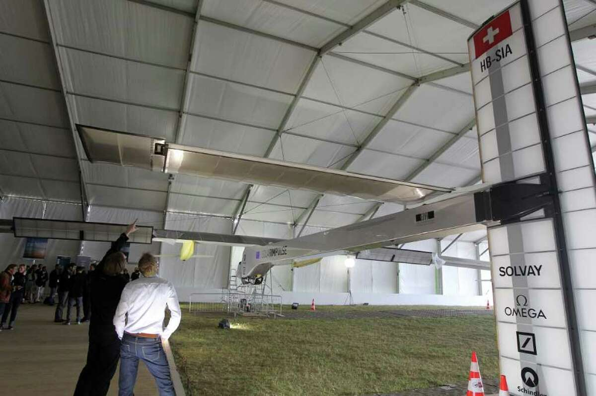 People look at the Swiss solar-powered aircraft Solar Impulse which is parked under a tent on June 23, 2011, at the International Paris Air show in Le Bourget airport, north of Paris. AFP PHOTO PIERRE VERDY
