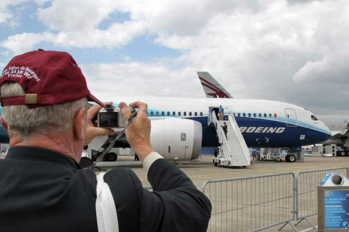 A man takes a picture of a Boeing 787 Dreamliner on the tarmac of the International Paris Air Show on June 23, 2011 in Le Bourget airport, north of Paris. The event will be open to the public from June 24 to June 26. AFP PHOTO PIERRE VERDY