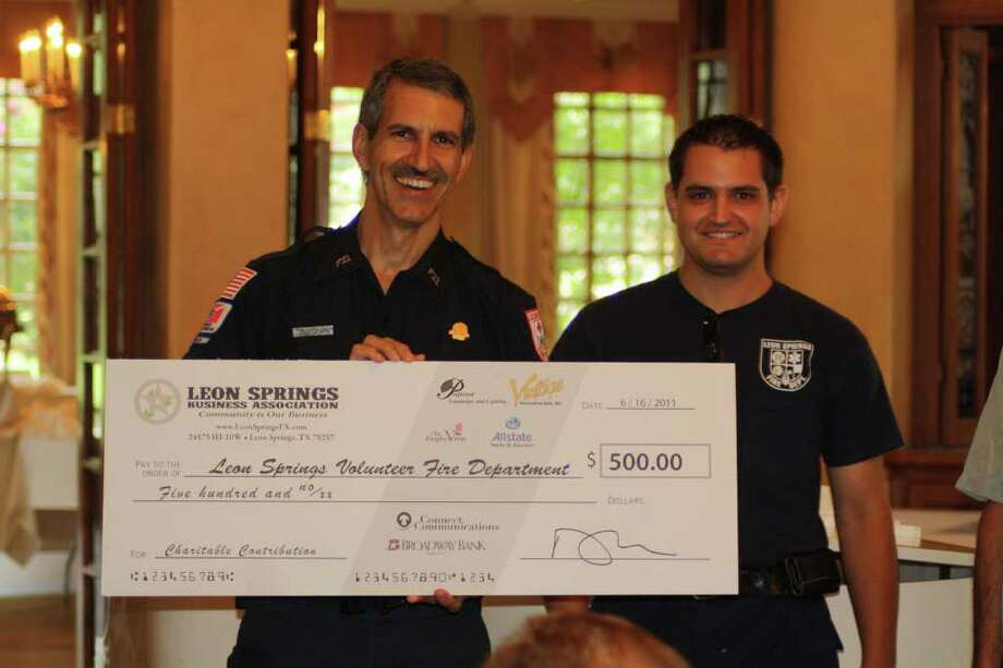 The LSBA presented a check to the Leon Springs Volunteer Fire Department and to Arms of Hope as an ongoing effort to support local charities and organizations in the Leon Springs area. Accepting for the LSVFD are Steve Biediger (left) and his son, Robert Biediger. Photo: Photo By Joni Simon