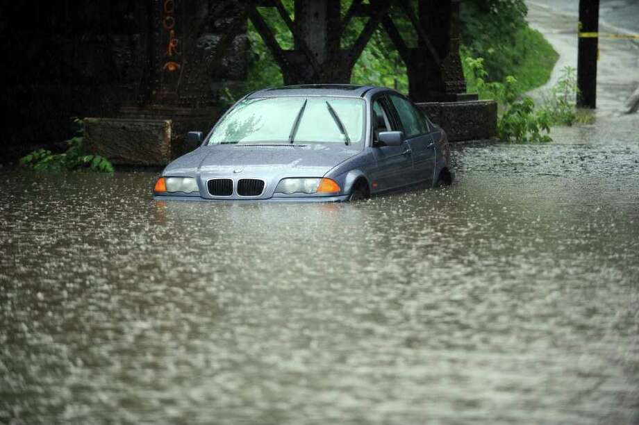 Heavy rains caused flooding in parts of Danbury Thursday, including under the West Street bridge where a motorist was standed. Photo taken Thursday, June 23, 2011. Photo: Carol Kaliff / The News-Times
