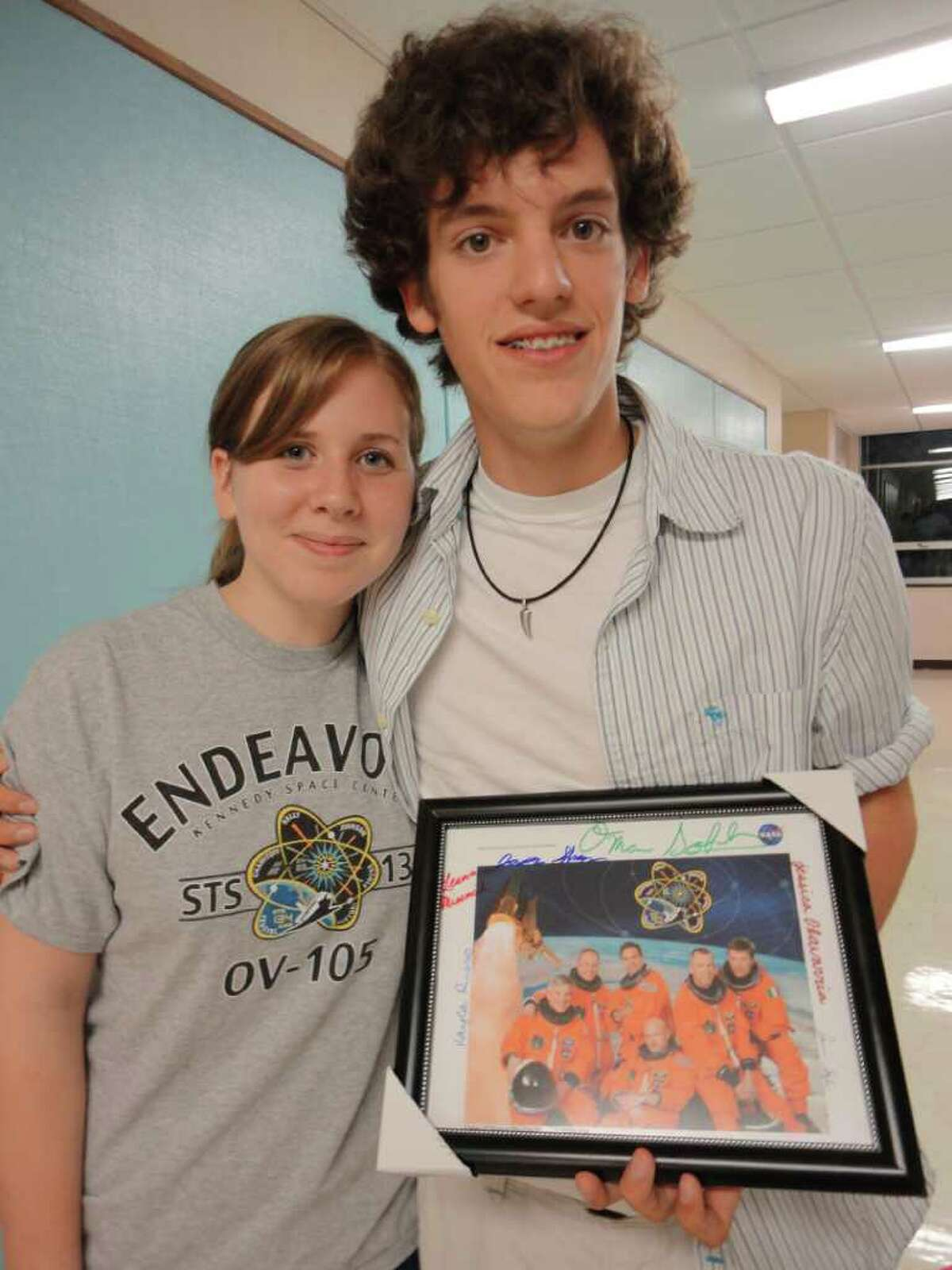 Kayla Russo and Jason Shnipes, were two of the four students who presented the results of their space shuttle experiment to the Board of Education Wednesday. Shnipes holds a photograph of the Endeavour astronauts, which the students, six in all, autographed and presented to board members, each of whom got their own photo.