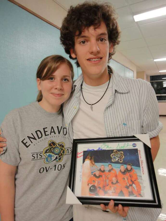 Kayla Russo and Jason Shnipes, were two of the four students who presented the results of their space shuttle experiment to the Board of Education Wednesday. Shnipes holds a photograph of the Endeavour astronauts, which the students, six in all, autographed and presented to board members, each of whom got their own photo. Photo: Meg Barone / Connecticut Post Freelance
