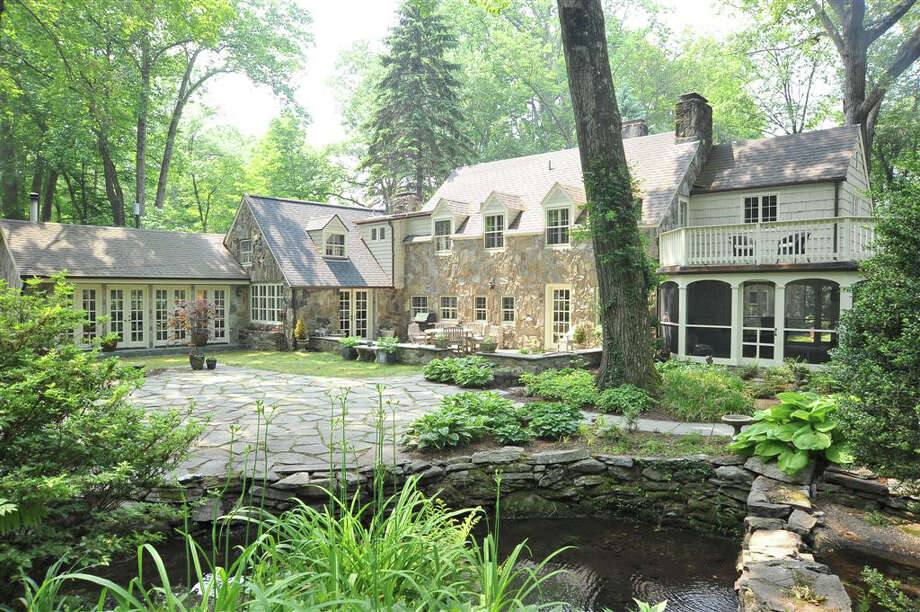 Pictured is the rear side of the home at 30 Charcoal Hill Road, which once belonged to famed architect Frazier Forman Peters, who was famous for his design and construction of stone houses from the 1920s to the 1950s. This house, now on the market, has over 5,000 square feet of living space and a brook running through the backyard. Photo: Alan Goldfinger