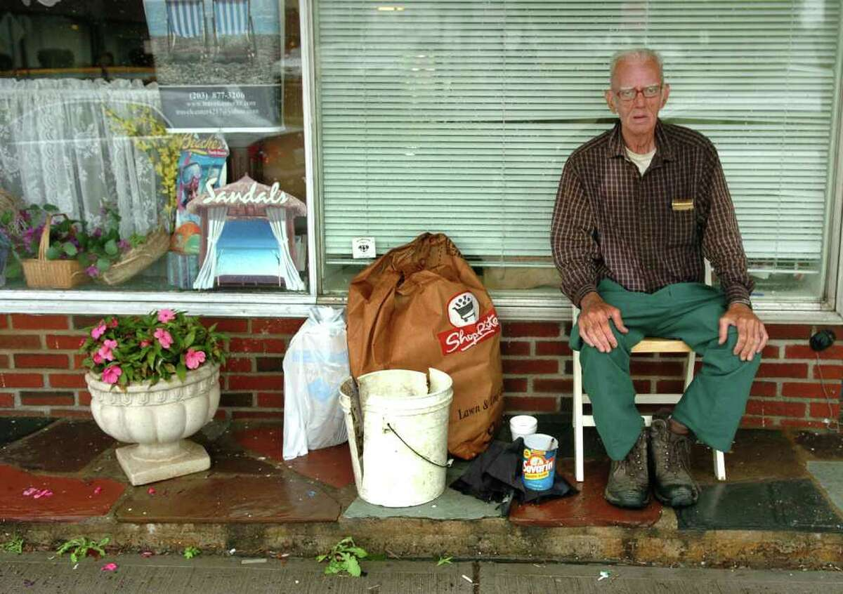 Waiting out the rain and trying to dry off a bit, Bill Casey, of Milford, sits under an awning at a business along River Street in Milford, Conn. on Wednesday June 23, 2011.