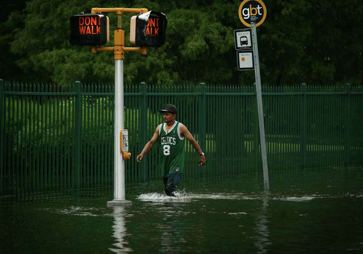 Sylvester Loyd of Stratford walks through knee deep flood water at the corner of Stratford and Bruce Avenues in Stratford on Thursday, June 23, 2011.