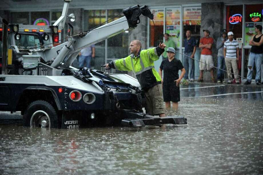 A tow truck driver Cooper Whiteside, from Advanced Auto Repair in Danbury rehooks a car that got stuck in flood waters under the West Street bridge in Danbury Thursday afternoon, June 23, 2011. Photo: Carol Kaliff / The News-Times