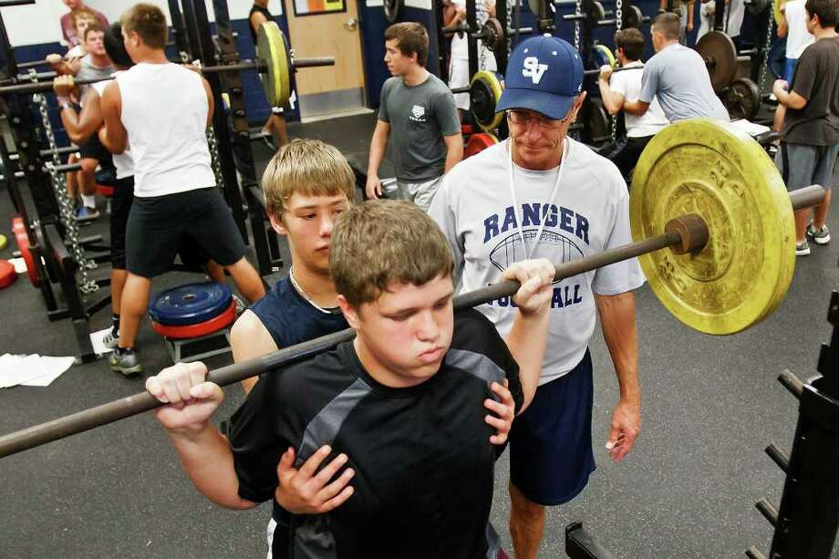 Smithson Valley coach Robert Teuton looks on as Ryan Godfrey (left) spots for Ty Wheeler as he does a squat lift in the Smithson Valley High School weight room on June 21, 2011.  The workout was part of the school's 2011 Summer Conditioning Program that runs from June 13-30 and July 11-28.  Approximately 550 kids in grades 7-12 are participating in the program.   Photo by Marvin Photo: Marvin Pfeiffer/Prime Time Newspapers