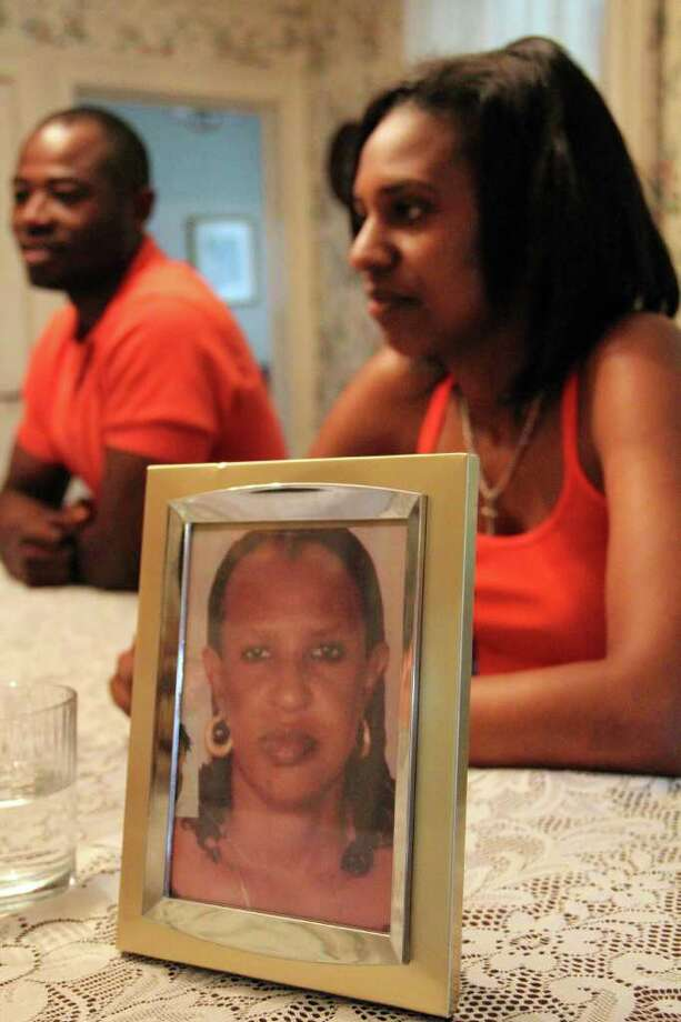 A framed picture of Rose Mukagakwya of Rwanda sits on a dining room table at a home in Duanesburg on Thursday, June 23, 2011. Mukagakwya was the mother of Grace Rutagengwa, background right, who came to the United States as a refugee. Rutagengwa was taken in by Robin DeVito, a teacher living in Duanesburg. Gafar Moumouni, originally of West Africa, background left, also lives in DeVito's home. (Erin Colligan / Special To The Times Union)