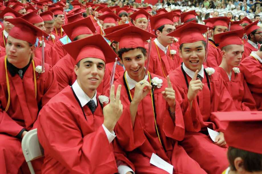 From left, Mike Guerrera, Rob Guinta and Jimmy Guo form the year 2011  with their fingers during the Masuk High School Graduation ceremony on Thursday June 23, 2011. Commencement ceremonies where held in the gymnasium due to rain. Photo: Lisa Weir / The News-Times Freelance