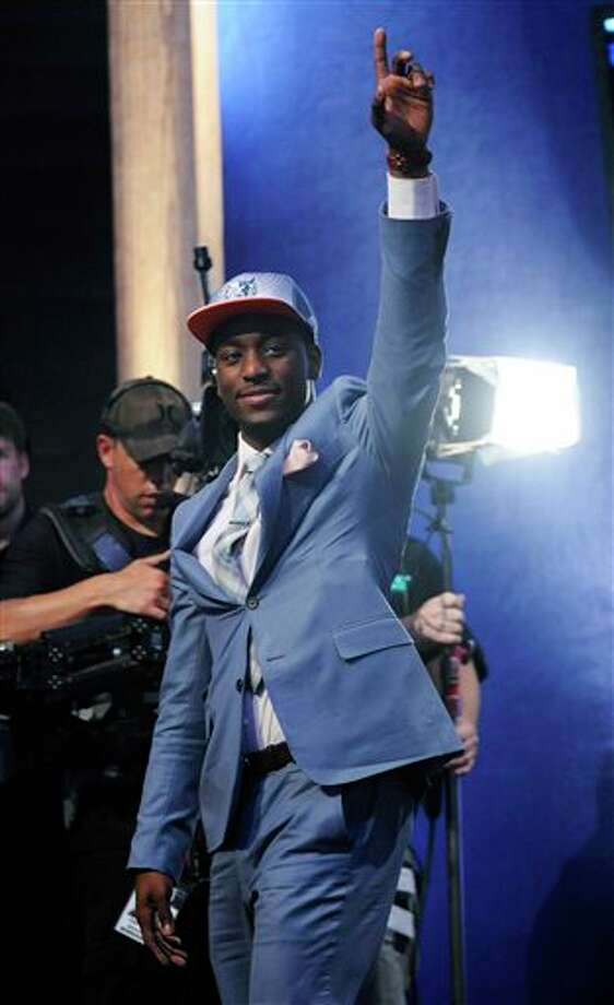 Connecticut's Kemba Walker, who was selected with the No. 9 pick by the Charlotte Bobcats, waves during the NBA basketball draft Thursday, June, 23, 2011, in Newark, N.J. (AP Photo/Bill Kostroun) Photo: AP